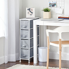 skinny white storage dresser with gray drawers, white desk, laptop, plant, trash can, chair, curtain