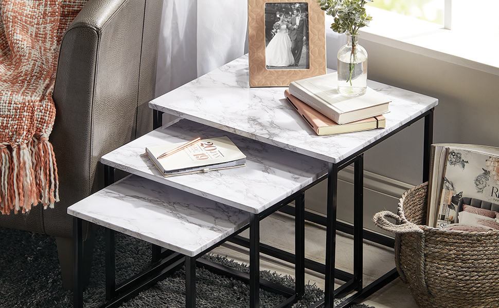 black nesting end tables, marble tops, photo frame, books, chair, blanket, basket, magazines, window